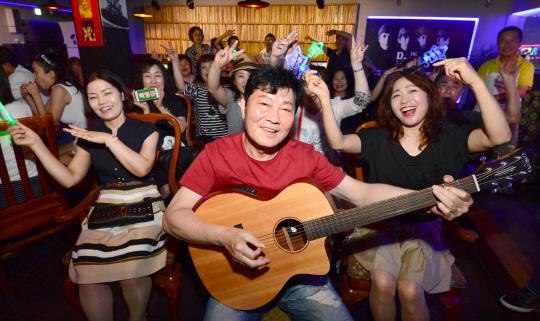 가수 백영규(가운데) 씨가 지난 3일 인천의 한 LP음악카페에서 라디오 팬클럽 '백가마' 회원들과 함께 최근 발매한 자신의 신곡 '술 한잔'을 열창하고 있다.  인천 = 신창섭 기자 bluesky@