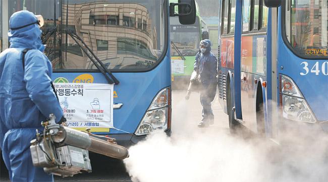 방역전문업체 직원들이 20일 오전 서울 강동차고지에서 신종 코로나바이러스 감염증(COVID-19) 확산을 막기 위해 소독작업을 하고 있다.   연합뉴스